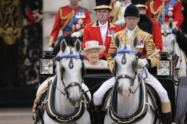 """Britain's Queen Elizabeth II rides in a carriage during the Trooping The Colour parade at Buckingham Palace, in London, Saturday, June 13, 2015. Hundreds of soldiers in ceremonial dress have marched in London in the annual Trooping the Color parade to mark the official birthday of Queen Elizabeth II. The Trooping the Color tradition originates from preparations for battle, when flags were carried or """"trooped"""" down the rank for soldiers to see. (AP Photo/Tim Ireland)"""