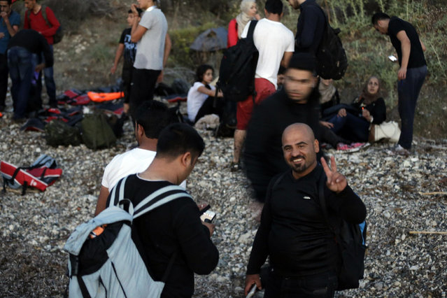 A Syrian migrant makes the victory sign after his arrival at a beach in Mytilene, on the northeastern Greek island of Lesvos, early Tuesday, June 16, 2015. Lesvos has been bearing the brunt of a huge influx of migrants from the Middle East, Asia and Africa. More than 50,000 migrants have arrived in Greece already this year, compared to the 6,500 in the first five months of last year. (AP Photo/Thanassis Stavrakis)
