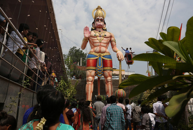 Hindu devotees watch as a 12 meter (40 feet) high statue of Hindu monkey-god Hanuman is washed during Hanuman Jayanti, the birthday of Lord Hanuman in Hyderabad, India, Friday, April 22, 2016. Hanuman is one of the most popular gods in the crowded pantheon of Hindu deities, and devout Hindus ascribe great strength and valor to him. (Photo by Mahesh Kumar A./AP Photo)