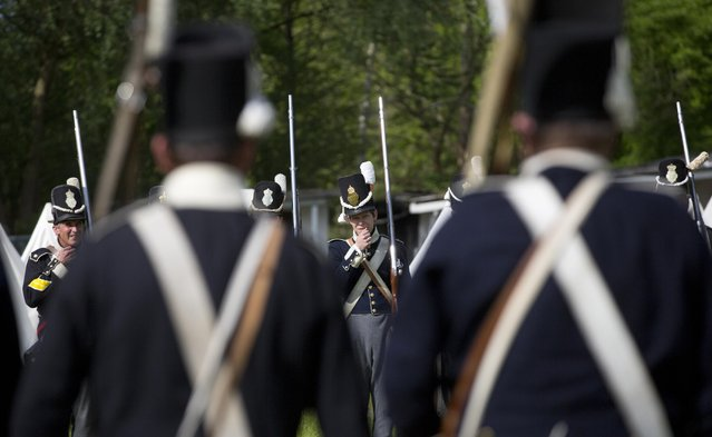 In this May 10, 2015, photo, historical re-enactors dressed as soldiers of the Belgian-Dutch 7th Battalion of the Line prepare to face off against each other in a mock battle at a Napoleonic era living history camp in Elewijt, Belgium. The Belgian-Dutch living history group is coordinating their group for participation in the 200th anniversary of the Battle of Waterloo which will take place in June 2015. (AP Photo/Virginia Mayo)