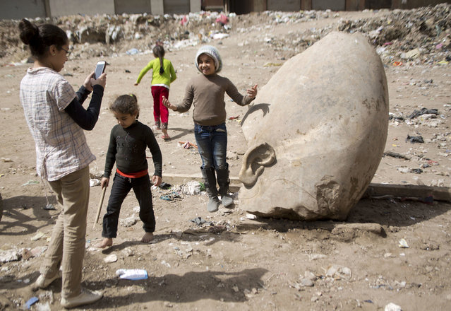 A child poses for a picture past a recently discovered statue in a Cairo slum that may be of pharaoh Ramses II, in Cairo, Egypt, Friday, March 10, 2017. (Photo by Amr Nabil/AP Photo)