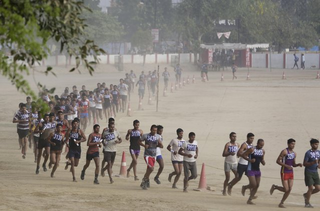Candidates, many barefoot and unable to afford running shoes, run to pass a fitness test during a recruitment drive for the Uttar Pradesh state police, in Allahabad, India, Tuesday, April 26, 2016. A state-wide recruitment process has recently been started to fill thousands of vacant police constable posts. (Photo by Rajesh Kumar Singh/AP Photo)