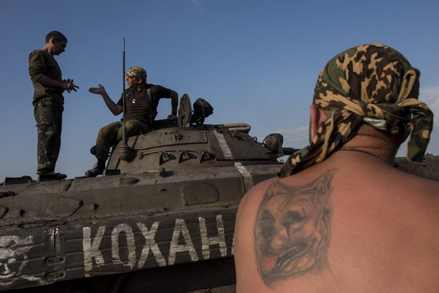 "In this photo taken Monday, June 22, 2015, Ukrainian servicemen from the Kiev-2 volunteer battalion talk atop an armored vehicle with a word on it saying ""my love"" in Ukrainian at the frontline in the village of Krymske, east Ukraine. (Photo by Evgeniy Maloletka/AP Photo)"