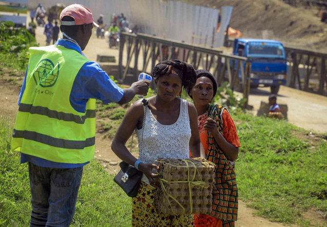 People crossing the border have their temperature taken to check for symptoms of Ebola, at the border crossing near Kasindi, eastern Congo Wednesday, June 12, 2019, just across from the Ugandan town of Bwera. In Uganda, a 5-year-old boy vomiting blood became the first cross-border victim of Ebola in the current outbreak on Wednesday, while two more people in Uganda tested positive for the highly contagious disease that has killed nearly 1,400 in Congo. (Photo by Al-hadji Kudra Maliro/AP Photo)