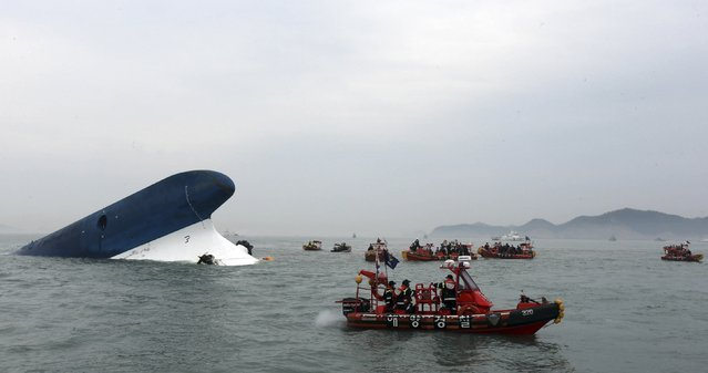 """Part of South Korean passenger ship """"Sewol"""" that has been sinking is seen as South Korean maritime policemen search for passengers in the sea off Jindo April 16, 2014. More than 100 people remained missing on Wednesday after a South Korean ferry with 477 people aboard capsized off the country's southwest coast, Yonhap news agency said. (Photo by Hyung Min-woo/Reuters/Yonhap)"""