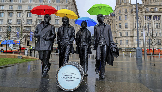 "Umbrellas are placed over the statute of the Beatles, during a photocall, on Liverpool's waterfront, in Liverpool, England, Wednesday, March 22, 2017. The city of Liverpool is getting set to celebrate the half-centenary of ""Sgt. Pepper's Lonely Hearts Club Band"", one of the most influential albums by local heroes The Beatles. (Photo by Peter Byrne/PA Wire via AP Photo)"