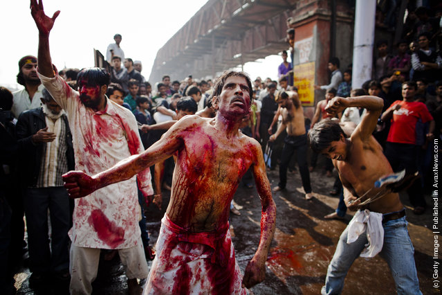 Shi'ite Muslim men and boys beat their chests as they practice self-flagellation during the religious ritual of Ashura in New Delhi, India