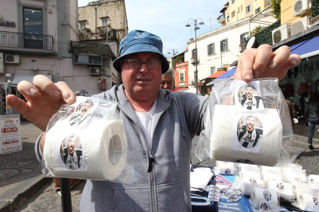 """A vendor shows toilet paper rolls with portraits of Juventus' Argentinian forward Gonzalo Higuain on March 23, 2017 in a street of Naples, Italy. Eight months after leaving team Napoli for Juventus Turin, Gonzalo Higuain prepares a hectic return for the Italian Seria A football match Napoli vs Juventus at San Paolo stadium, where the rancor against the Argentine """"traitor"""" remains immense. (Photo by Carlo Hermann/AFP Photo)"""