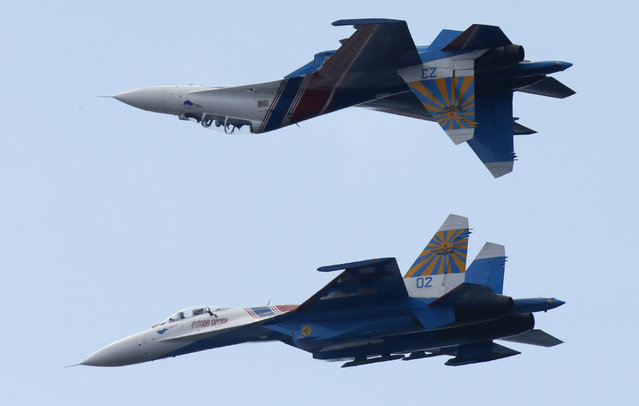 Su-27 jets of aerobatics team Russkiye Vityasy, or Russian Knights perform during an air show at the International Maritime Defence show in St.Petersburg, Russia, Sunday, July 5, 2015. (Photo by Dmitry Lovetsky/AP Photo)