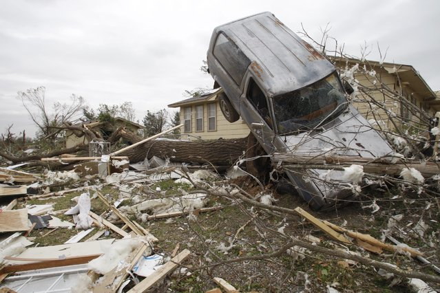This Friday, April 15, 2011, file photo, shows an SUV that has come to rest on a tree in Tushka, Okla. A large section of the Midwest and South are at risk for strong tornadoes, severe thunderstorms and flash flooding this weekend, forecasters say. (Photo by Sue Ogrocki/AP Photo)
