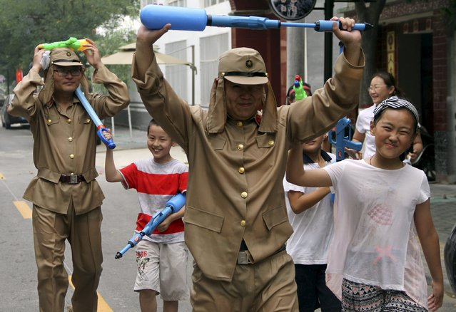 Staff of a tourism resort dressed as Japanese soldiers raise their water guns to surrender as they take part in a mock fight with children visitors during an event to mark the 70th anniversary of the end of the Sino-Japan War, in Binzhou, Shandong province, China, July 5, 2015. (Photo by Reuters/Stringer)