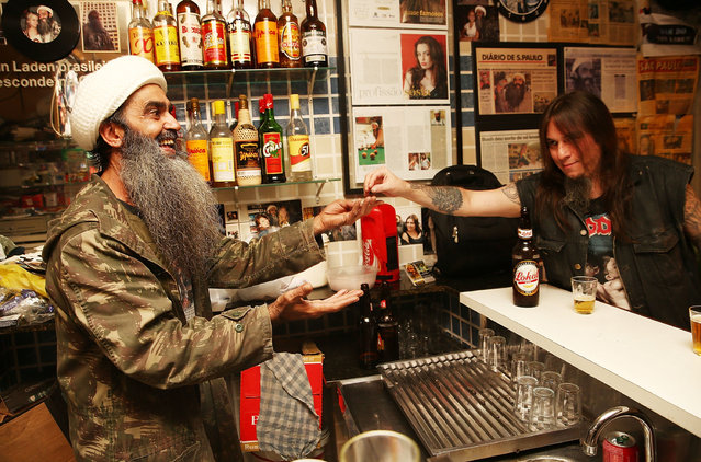 """Osama bin Laden lookalike Ceara Francisco Helder Braga Fernandes (L) receives payment in his """"Bar do Bin Laden"""" on April 29, 2014 in Sao Paulo, Brazil. Braga says he was known as the """"Beard Man"""" before 9/11 but became known as a Bin Laden lookalike following the 9/11 attacks. He says he is Christian and continues to play the role to support his business. (Photo by Mario Tama/Getty Images)"""