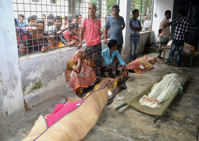 An elderly woman grieves next dead bodies at Mymensingh Medical College Hospital in the town of Mymensingh, 115 kilometers (70 miles) north of Dhaka, Bangladesh, Friday, July 10, 2015. The victims died on a stampede when hundreds of people stormed the home of a businessman for a charity handout during the holy Muslim month of Ramadan, police said. (Photo by Jahangir Kabir Jewel/AP Photo)