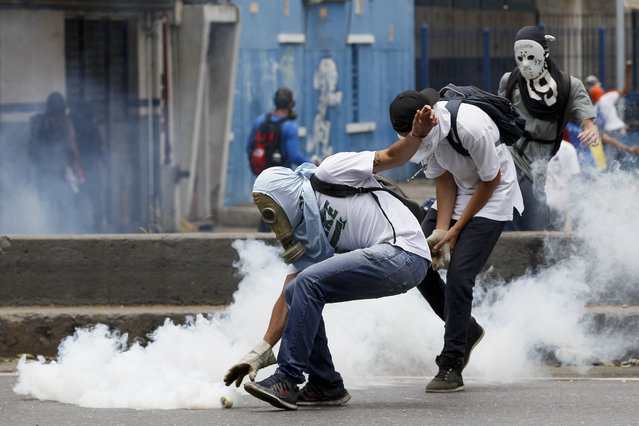 A demonstrator picks up a canister of tear gas launched by security forces during anti-government protests in Caracas, Venezuela, Wednesday, April 19, 2017. (Photo by Ariana Cubillos/AP Photo)