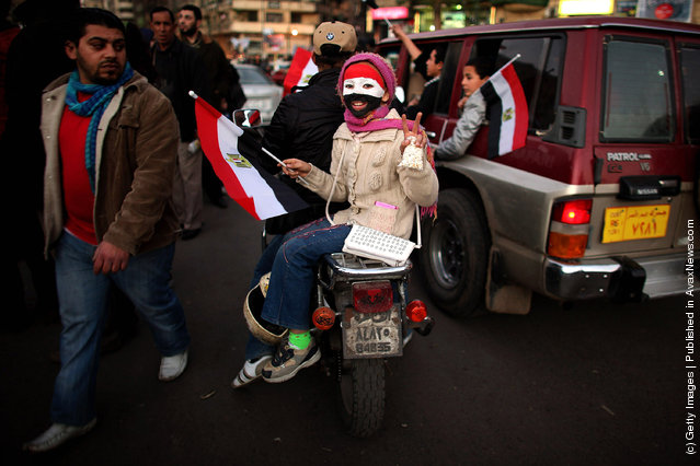 A young girl rides on the back of a motorcycle through Tahrir Square