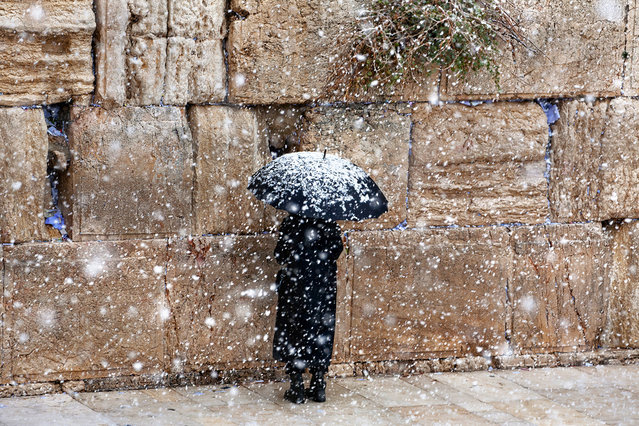 """Faith"". A dedicated man praying all alone under a heavy snowfall, at the usually crowded Western Wall in Jerusalem. The Western Wall, the only remnant of the Holy Temple of Jerusalem (destroyed in 70 CE), is the holiest site for the Jewish people. It is visited by huge crowds of worshipers and tourists almost every day. Photo location: Jerusalem, Israel. (Photo and caption by Noam Chen/National Geographic Photo Contest)"