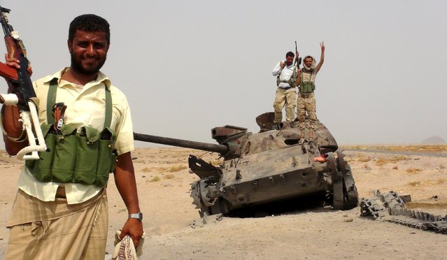 Southern Resistance fighters stand with a tank destroyed during fighting against Houthi fighters in the Emran outskirts of Yemen's southern port city of Aden July 13, 2015. (Photo by Reuters/Stringer)