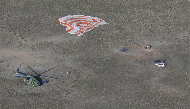 A rescue team arrives as the Russian Soyuz TMA-11M space capsule rests on the ground shortly after landing south-east of the town Dzhezkazgan,  Kazakhstan, May 14, 2014. A Soyuz space capsule with Japanese astronaut Koichi Wakata, Russian cosmonaut Mikhail Tyurin and U.S. astronaut Rick Mastracchio, returning from a five-month mission to the International Space Station, landed safely Wednesday on the steppes of Kazakhstan. (Photo by Dmitry Lovetsky/Reuters)