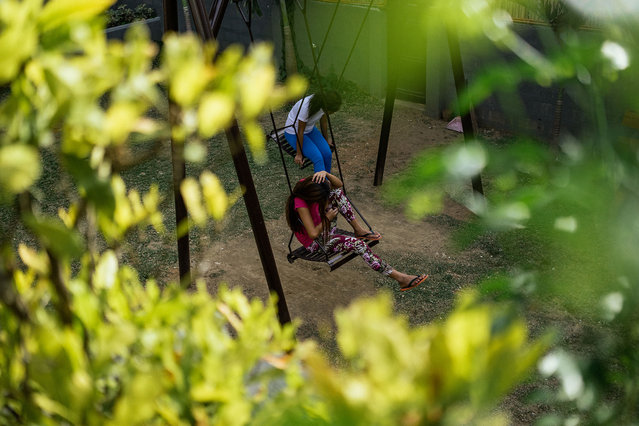 Young Filipina girls who used to work in the s*x industry sit in the swings at a halfway house in Manila. (Photo by Hannah Reyes Morales/The Washington Post)
