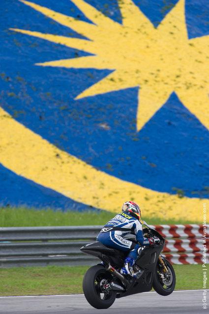 Katsuyuki Nakasuga of Japan and Yamaha Factory Racing lifts the front wheel during the third day of MotoGP testing at Sepang Circuit