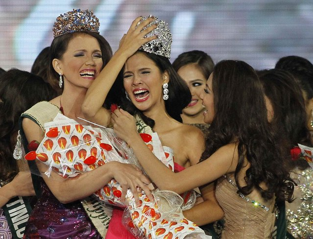 Jamie Herrel (C) of Cebu city, central Philippines, holds onto her crown as she is congratulated by other candidates after being crowned as Miss Philippines-Earth 2014 on coronation night in Manila May 11, 2014. Herrel, competed against 49 other candidates for the top post of Miss Philippines-Earth and will represent the country in the coming 2014 Miss Earth beauty pageant which advocates in preserving the environment, local media reported. (Photo by Romeo Ranoco/Reuters)