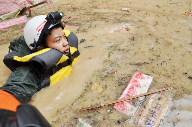This picture taken on July 15, 2015 shows a rescuer making his way through floodwaters after heavy rainfall hit the area in Songtao county in Tongren, in southwest China's Guizhou province. (Photo by AFP Photo/Stringer)