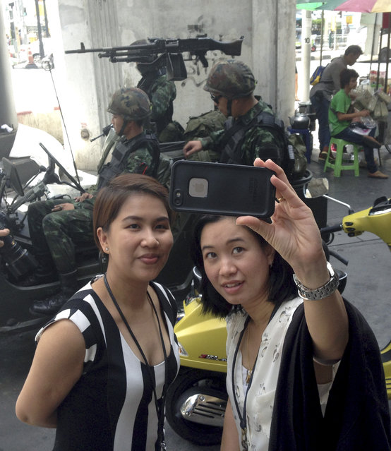 Residents stop to take a photograph of themselves at a military checkpoint in central Bangkok, Thailand, Tuesday, May 20, 2014. Thailand's army declared martial law in a surprise announcement before dawn Tuesday that it said was aimed at keeping the country stable after six months of sometimes violent political unrest. The military, however, denied a coup d'etat was underway. (Photo by Kiko Rosario/AP Photo)