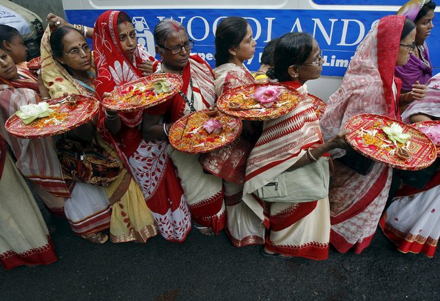 Hindu devotees carry trays of offerings as they wait to participate in the annual Rath Yatra, or chariot procession, in Kolkata, India, July 18, 2015. (Photo by Rupak De Chowdhuri/Reuters)