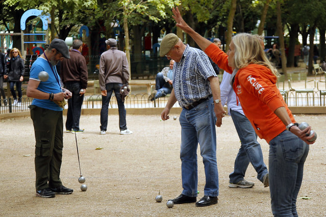 """In this Tuesday, June 23, 2015 photo, Andrea throws a boule during an amateur Petanque match in Paris. In the game, the goal is to throw hollow metal balls as close as possible to a small wooden ball, called a """"cochonnet"""" (piglet), while standing inside a circle with both feet on the ground. (Photo by Francois Mori/AP Photo)"""