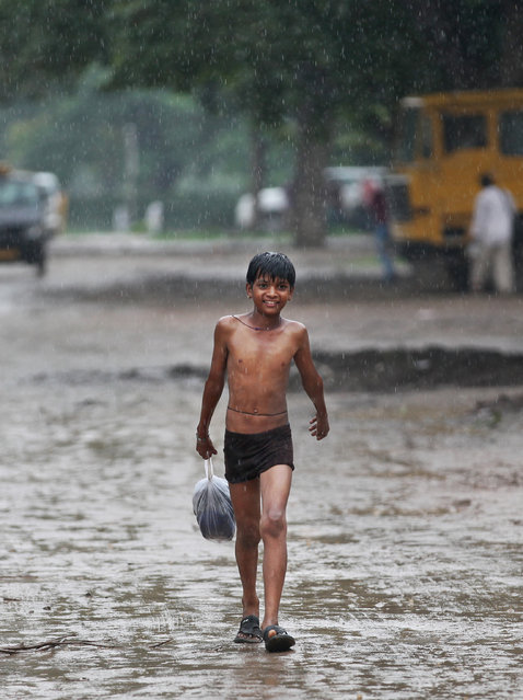 An Indian boy walks during sudden downpour in New Delhi, India, Friday, July 10, 2015. India's monsoon season, which runs from June to September, bring rains that are vital to agriculture. (Photo by Altaf Qadri/AP Photo)