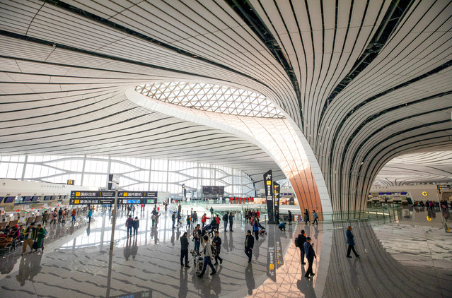 Visitors walk in the Beijing Daxing International Airport in Beijing, China, 27 October 2019. Beijing International Daxing Airport will commence its first international flights on 27 October 2019 as many domestic and international airlines began operations at the new airport. The US$63 billion (56.8 billion euros) airport designed by renown Iraqi-born architect Zaha Hadid consists of four runways and is expected to facilitate up to 72 million passengers a year by 2025. (Photo by How Hwee Young/EPA/EFE)