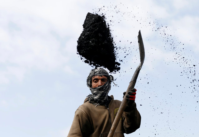 A labourer unloads coal from a truck at a coal dump site on the outskirts of Kabul, Afghanistan March 7, 2017. (Photo by Mohammad Ismail/Reuters)