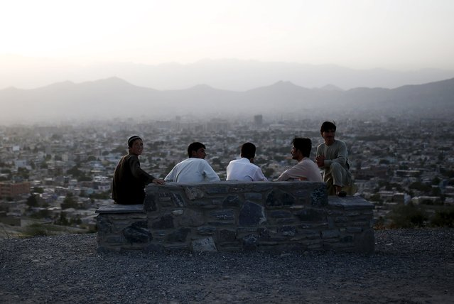 Men sit on a hill overlooking parts of Kabul city, Afghanistan July 22, 2015. (Photo by Ahmad Masood/Reuters)