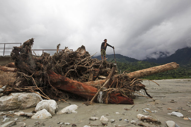 A Nepalese man stands on a foot bridge destroyed by flood waters in Thulakhet, near Pokhara in Nepal, Friday, July 31, 2015. (Photo by Niranjan Shrestha/AP Photo)
