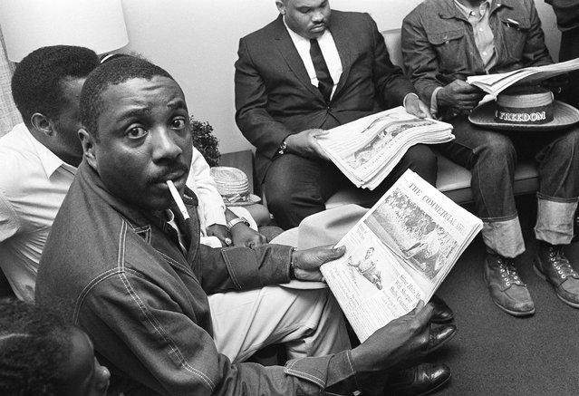 Chicago comedian Dick Gregory, wearing denim jacket and western attire, reads a Memphis newspaper as he waits in the administrator's office, June 7, 1966 at William F. Bowld Hospital in Memphis for word of James Meredith's condition. Gregory arrived in Memphis from Chicago with the announced purpose of taking up Meredith's Memphis-to-Jackson, Miss., march at the point, where Meredith was shot on Monday afternoon. (Photo by Charles Kelly/AP Photo)