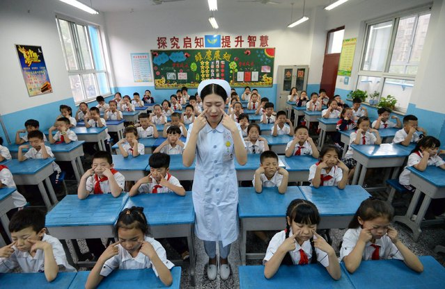 A hospital staff member teaches primary school children how to do eye exercises, at a primary school in Handan, in China's northern Hebei province on June 5, 2017. (Photo by AFP Photo/Stringer)