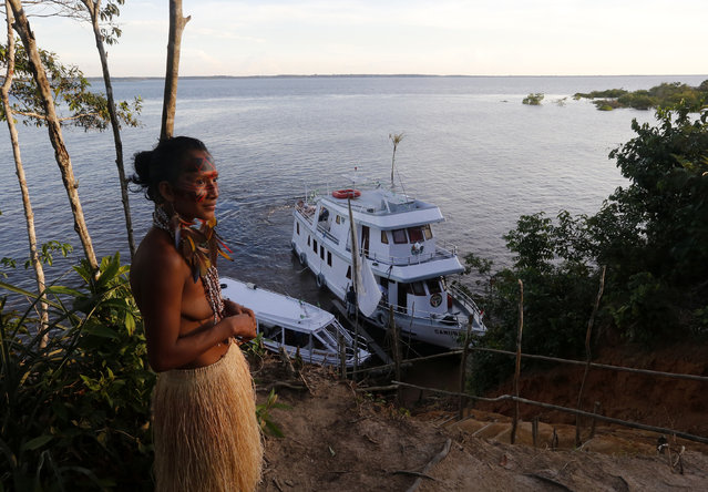 A member of the Amazonian Tatuyo tribe looks on as tourists arrive in a boat to her village in the Rio Negro (Black River) near Manaus city, a World Cup host city, June 23, 2014. Because of their proximity to host city Manaus and their warm welcome, the Tatuyo have enjoyed three weeks of brisk business thanks to the World Cup. Usually, they host between 10 and 30 tourists a day. During the World Cup, this number has rocketed to 250 a day, They have become richer and other communities now come to them to sell them juices and fishes. (Photo by Andres Stapff/Reuters)