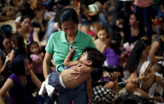 "A mother breastfeeds her child in Mandaluyong city, Metro Manila in the Philippines August 1, 2015"". (Photo by Erik De Castro/Reuters)"