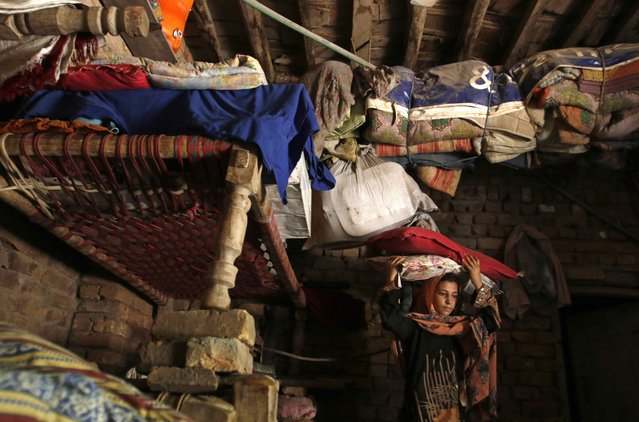 A girl moves bedding to top bunks at her home after heavy rainfall caused flooding in Peshawar, Pakistan, July 27, 2015. (Photo by Khuram Parvez/Reuters)