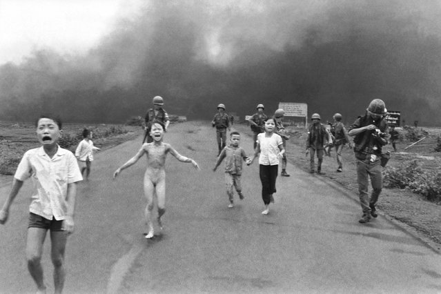 South Vietnamese forces follow after terrified children, including 9-year-old  Kim Phuc, center, as they run down Route 1 near Trang Bang after an aerial napalm attack on suspected Viet Cong hiding places, June 8, 1972.  A South Vietnamese plane accidentally dropped its flaming napalm on South Vietnamese troops and civilians. The terrified girl had ripped off her burning clothes while fleeing. The children from left to right are: Phan Thanh Tam, younger brother of Kim Phuc, who lost an eye, Phan Thanh Phouc, youngest brother of Kim Phuc, Kim Phuc, and Kim's cousins Ho Van Bon, and Ho Thi Ting.  Behind them are soldiers of the Vietnam Army 25th Division. (Photo by Nick Ut/AP Photo)