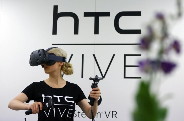 A woman checks a pair of Vive Virtual Reality goggles, produced by Taiwan's HTC, during the Gamescom 2015 fair in Cologne, Germany August 5, 2015. (Photo by Kai Pfaffenbach/Reuters)