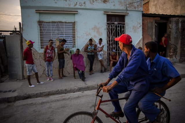 In this March 20, 2015 photo, state workers share a bicycle as they ride past a barber cutting hair on the sidewalk, after their work shifts in Santiago, Cuba. There are more horse-drawn carts and bicycles than cars and tourist buses on the two-lane road from Havana to Santiago. (Photo by Ramon Espinosa/AP Photo)