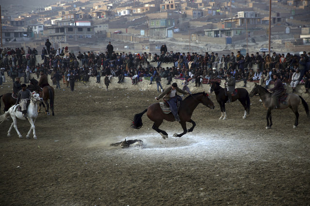 Afghan horse riders compete for the goat during a friendly buzkashi match on the outskirts of Kabul, Afghanistan, Friday, December 27, 2019. Buzkashi is a traditional and the national sport of Afghanistan, where players compete to place a goat carcass into a goal circle. It was banned during the Taliban rule. (Photo by Rahmat Gul/AP Photo)