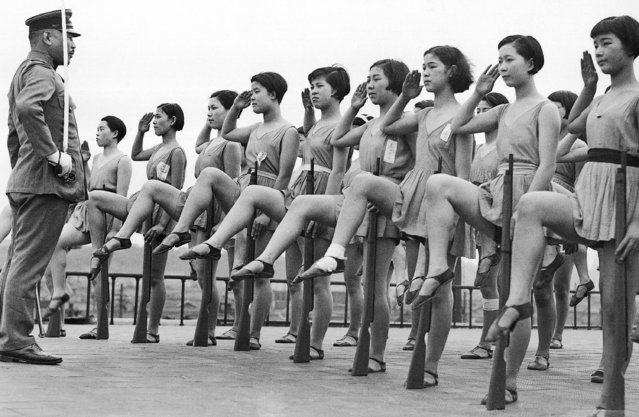 Japanese chorus girls appear to be drilling in military tactics atop their theater building as they perform salutes, June 30, 1937. The officer is from the Japanese regular army and says the girls display more rhythm in their drills than do the regular troops. (Photo by AP Photo)