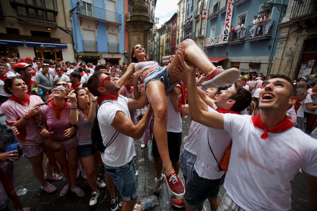 "Revelers throw a woman to the air during the opening and the firing of the ""Chupinazo"" rocket which starts the 2014 Festival of the San Fermin Running of the Bulls on July 6, 2014 in Pamplona, Spain. The annual Fiesta de San Fermin, made famous by the 1926 novel of US writer Ernest Hemmingway entitled ""The Sun Also Rises"", involves the daily running of the bulls through the historic heart of Pamplona to the bull ring. (Photo by Pablo Blazquez Dominguez/Getty Images)"