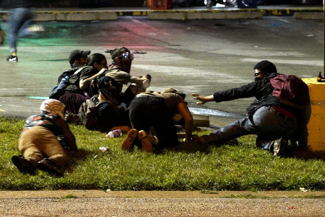 Protesters fall to the ground to take cover after shots were fired in a police-officer involved shooting in Ferguson, Missouri August 9, 2015. (Photo by Rick Wilking/Reuters)