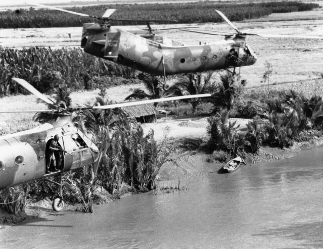 U.S. door gunners in H-21 Shawnee gunships look for a suspected Viet Cong guerrilla who ran to a foxhole from the sampan on the Mekong Delta river bank, Jan. 17, 1964