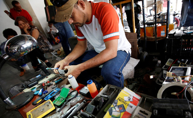 A man repairs a mobile phone at a second-hand market in Caracas, Venezuela, June 26, 2016. (Photo by Mariana Bazo/Reuters)