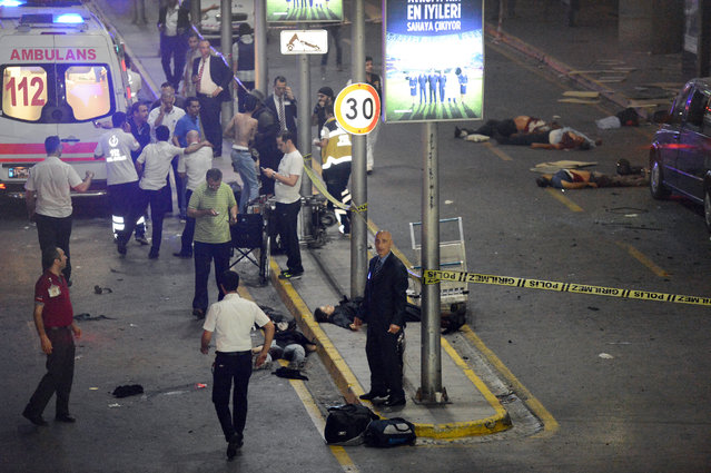 Medics and security members work at the entrance of the Ataturk Airport after explosions in Istanbul, Tuesday, June 28, 2016. (Photo by IHA via AP Photo)