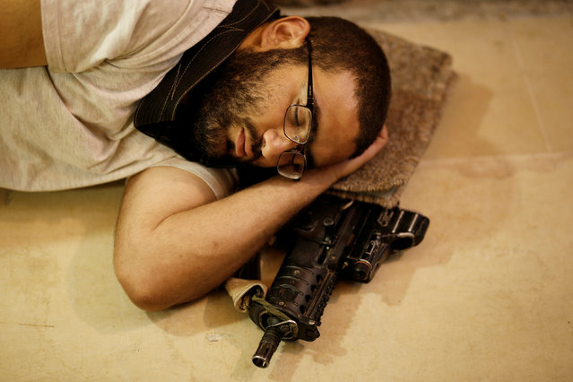 A Jewish worshipper sleeps next to his weapon near the Western Wall on Tisha B'Av, a day of fasting and lament, in Jerusalem's Old City August 1, 2017. (Photo by Amir Cohen/Reuters)